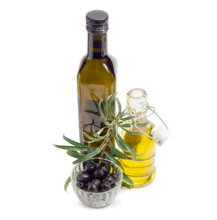 Black olives in small glass bowl, one dark glass bottle and one small bottle with open lid of the olive oil and olive branch beside on a white background Stock Photo