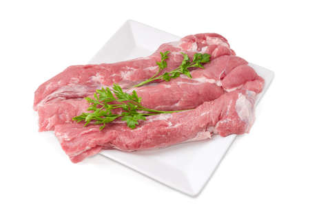 Three pieces of uncooked pork tenderloin with twigs of parsley on a big square white dish on a white background