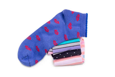 Blue womens low cut socks on a stack of other varicolored socks on a white background