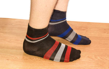 Legs of teenager in different mens socks on a wooden floor on a white background