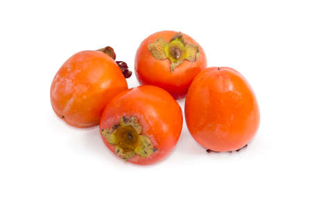 Several ripe freshly harvested persimmons on a white background