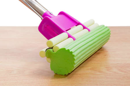 Green sponge on plastic mop with mounting clamp closeup on a wooden floor on a white background Stock Photo