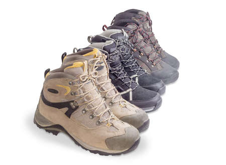 Three different pairs of boots for trekking put in a row on a white background  Stock Photo