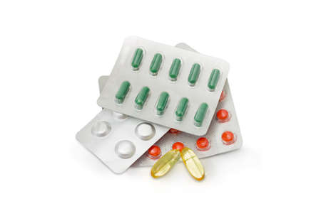 semitransparent: Yellow translucent capsules and blister packs with different medications on a white background