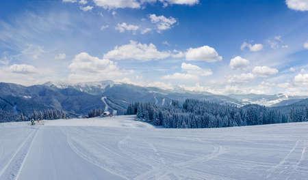 Gestreepte voorbereide skihelling op een achtergrond van bergketens en hemel op skitoevlucht in Karpatische Bergen