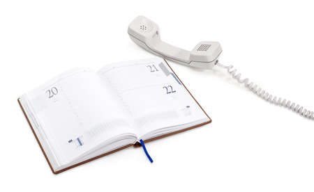 Open business diary and white handset of the landline telephone  lying down beside on a white background