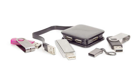 External separate USB hub in black square plastic casing with short cable and several different usb flash drives on a white background  Banco de Imagens