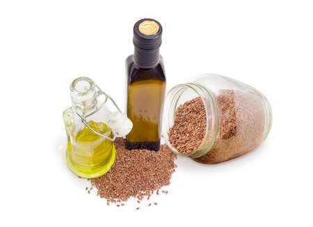 Dark gllass bottle and transparent gllass bottle with open lockable lid of the flaxseed edible oil, gllass jar and pile of linseeds beside on a white background