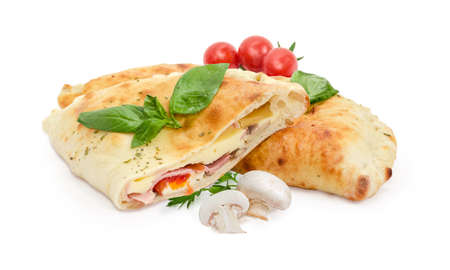 Half and whole of the baked calzone - closed type of pizza that is folded in half, decorated with basil and parsley twigs, raw mushrooms and cherry tomatoes on a white background