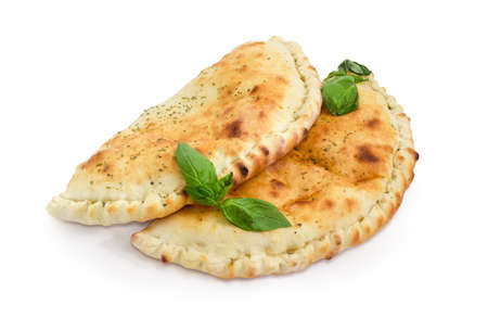 Two baked calzone - closed type of pizza that is folded in half decorated with basil twigs on a white background  Stock Photo
