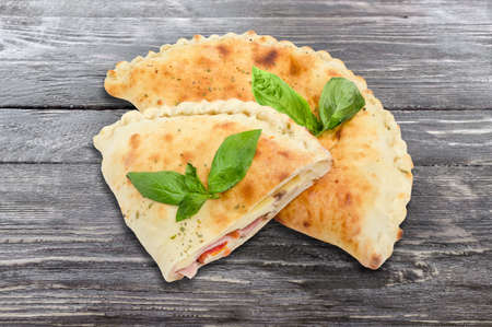 One whole and half of the baked calzone - closed type of pizza that is folded in half decorated with basil twigs on a vintage wooden planks