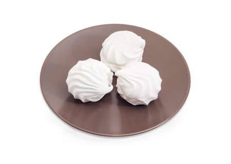 White zefir - Eastern European soft confectionery similar to marshmallow on the brown dish on a white background