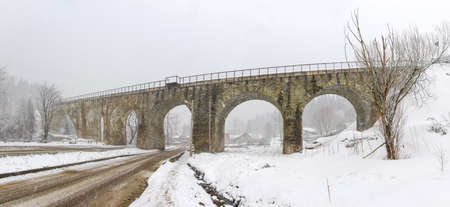 Old railway viaduct made of stone masonry over valley with highway in Carpathian Mountains during heavy snowfall  Stock Photo