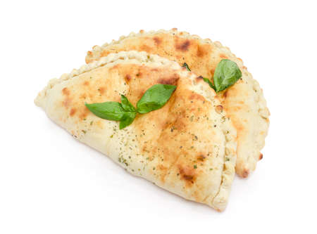 Two baked calzone - closed type of pizza that is folded in half decorated with basil twigs on a white background
