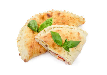 One whole and half of the baked calzone - closed type of pizza that is folded in half decorated with basil twigs on a white background  Reklamní fotografie