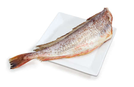 Carcass of the uncooked red cod without heads and purified from fish scale on the large square white dish on a white background