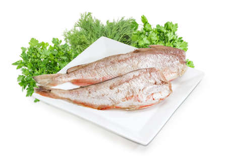 Two carcasses of uncooked red cod without heads and purified from fish scale on the large square white dish against of bundles of the parsley, dill, cilantro on a white background Stock Photo