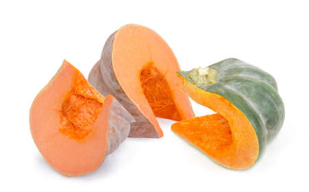 Two pieces of the orange pumpkin and one piece of the winter squash with dark green rind on a white background