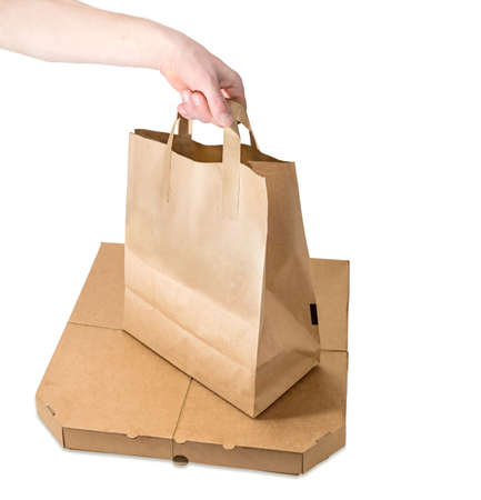 Packaging for meals delivery - paper bag in hand over the pizza box tied with twine on a white background