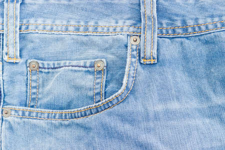 Fragment of the top of the old light blue jeans with waistband, two belt loops, reinforcing by copper rivets pocket and  little pocket