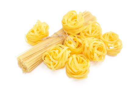 Several uncooked dried noodle nests and bunch of the long pasta bound with twine on a white background