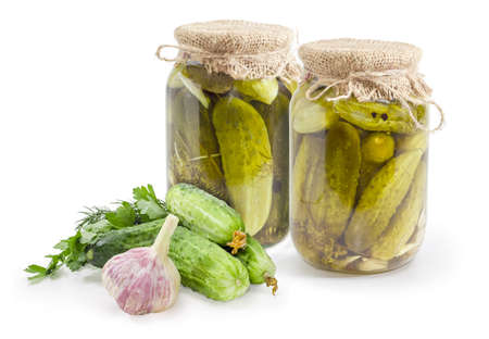 Canned cucumbers with spices in two glass jars and fresh cucumbers, herbs and garlic beside on a white background