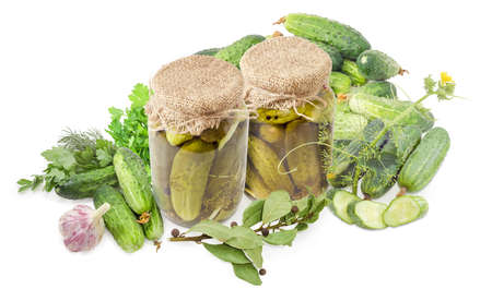 Canned cucumbers with spices in two glass jars and fresh cucumbers, herbs, spices and garlic on a white background