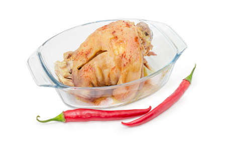 Baked ham hock in glass casserole pan and two pods of chili beside on a white background  Stock Photo
