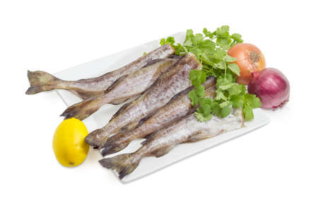 Several uncooked carcasses of the Alaska pollock without of heads and twig of cilantro on a big square white dish and lemon, two different onions beside on a white background