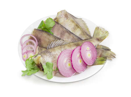 Several uncooked carcasses of the notothenia fish without of the heads, cilantro twigs and round slices of red onion on a white dish on a white background