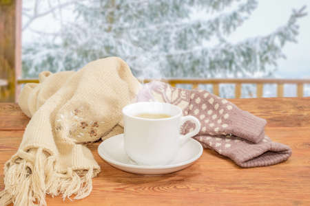 White cup of coffee with cream, womens woolen mittens and knitted scarf on an old wooden rustic table on background of snow-covered spruce outdoor