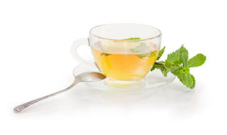 Transparent glass cup of tea with mint leaves and twig of fresh mint separenely on the glass saucer with tea spoon on a white background
