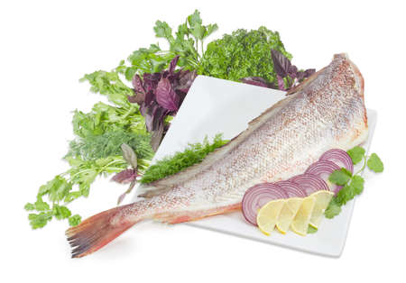 Carcass of the uncooked red cod without head, sliced lemon and red onion on the large square white dish, cilantro, basil, parsley and dill twigs on a white background  Stock Photo