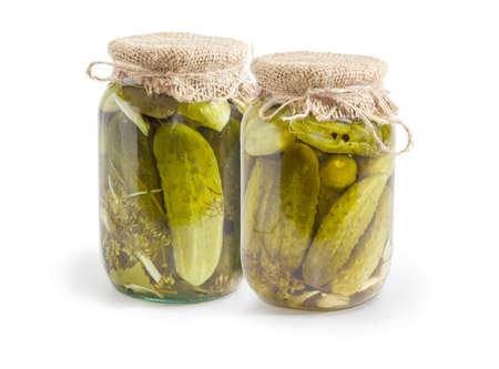 Canned cucumbers with spices in two glass jars on a white background