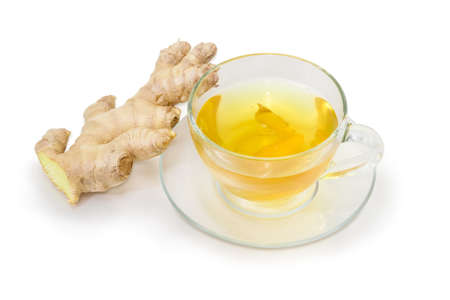 Ginger tea in a glass transparent cup on a glass saucer and fresh ginger root on a white background
