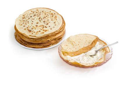 Thin round pancake on a pink glass dish during rolling up with cottage cheese filling and stack of other not rolled pancakes on a white background