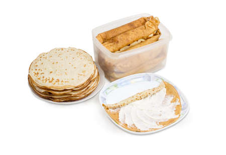 Thin round pancake on a dish during rolling up with cottage cheese filling, stack of not rolled pancakes and rolled up pancakes in plastic container on a white background  Stock Photo