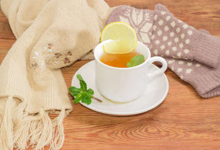Cup of tea with lemon slice and mint leaf on saucer with mint twig, womens woolen mittens and knitted scarf on an old wooden rustic surface