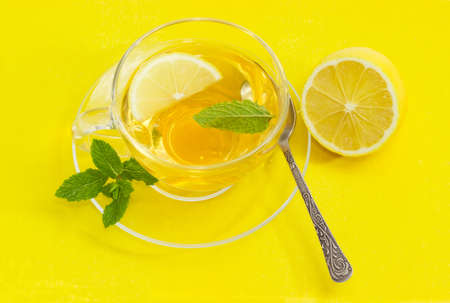 Top view of the glass cup of tea with mint leaf and and lemon slice on the glass saucer with spoon and mint twig and half of lemon separately on a yellow background