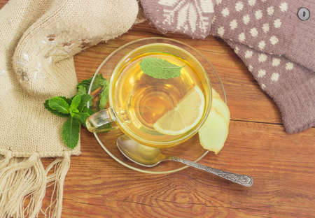 Top view of the glass cup of tea with lemon and ginger root slices, mint leaf on glass saucer with spoon on a rustic wooden table beside of the women's woolen mittens and knitted scarf outdoor