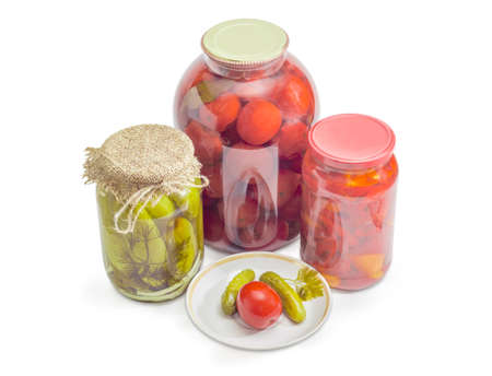 Two canned cucumbers and tomato on saucer against of glass jars of canned cucumbers, tomatoes and sliced bell peppers on a white background