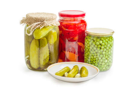 Three canned cucumbers with cloves of garlic on saucer on background of different glass jars of canned cucumbers, bell pepper and green peas on a white background