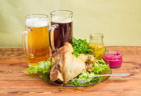 Baked ham hock on a dark glass dish with greens and fork, two glass mugs of lager beer and dark beer, small glass jars of beet horseradish sauce and French mustard on an old rustic wooden table