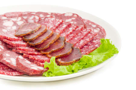 Fragment of white dish with sliced dried pork tenderloin, different salami and smoked sausage on lettuce leaf closeup at shallow depth of field on a white background Stock Photo