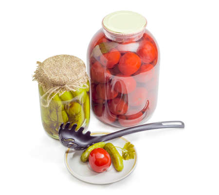 Two canned cucumbers and tomato on saucer with black plastic slotted spoon and two glass jars different sizes of canned cucumbers and tomatoes on a white background