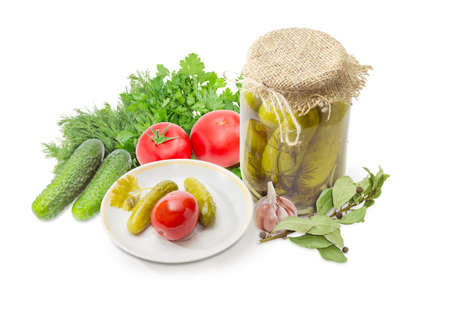 Canned cucumbers and tomato on saucer and glass jars of canned cucumbers among of the fresh cucumbers and tomatoes, dill, parsley, garlic and spices on a white background