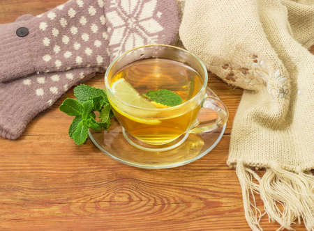 Glass transparent cup of tea with lemon slice and mint leaf on a saucer with mint twig on a rustic wooden table beside of the womens woolen mittens and knitted scarf