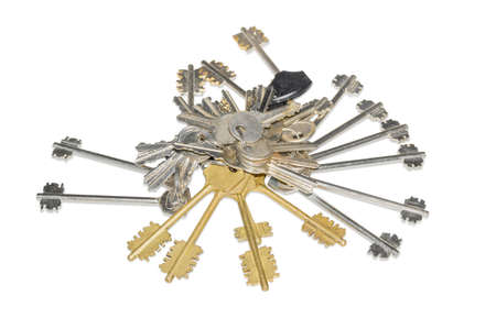 Pile of the different keys from door locks at shallow depth of field on a white background