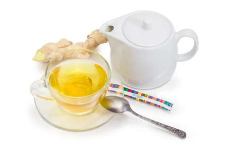 Green tea with ginger slices in a glass transparent cup on a glass saucer with tea spoon, white porcellaneous teapot, small sugar packet and fresh ginger root on a white background
