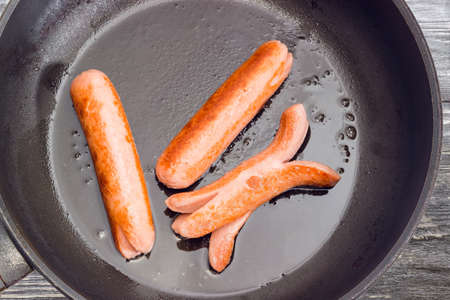 Top view of the fragment of frying pan with three fried vienna sausages on it closeup